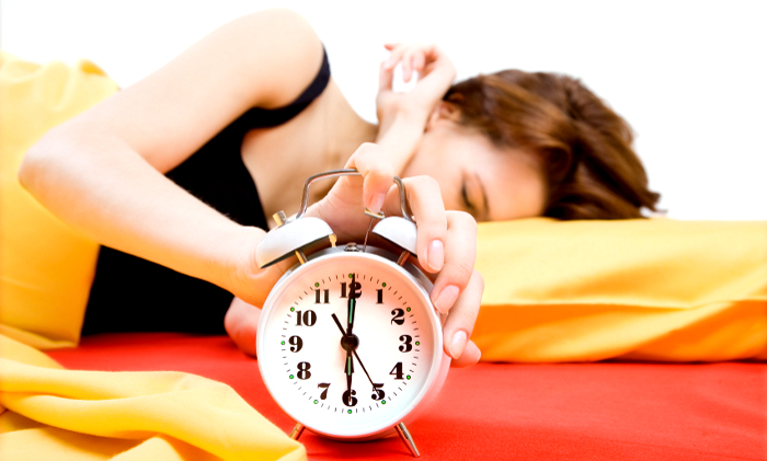 Young adult beautiful woman switching off alarm clock